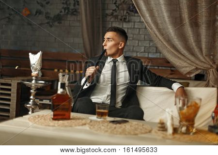 Young Stylish Man In A Suit Rests In The Bar. Man Drinking Whiskey And Smoking A Hookah.