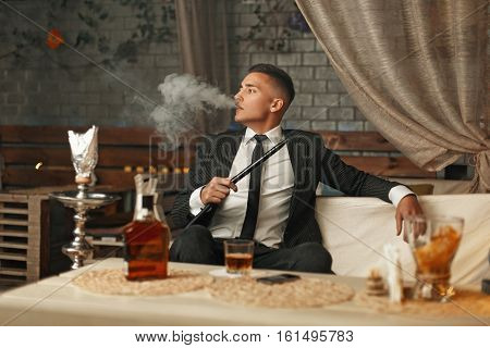 Handsome Stylish Man In A Suit Smoking A Hookah