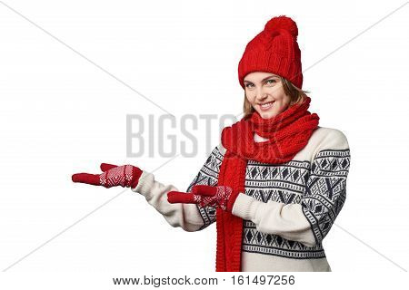 Happy woman wearing knitted warm scarf and hat showing open hand palm with copy space for product or text, looking at camera, over white background