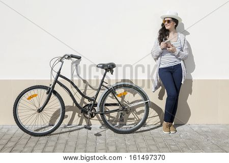 Young female tourist with smartphone standing nearby bike against wall in Lanzarote Spain.