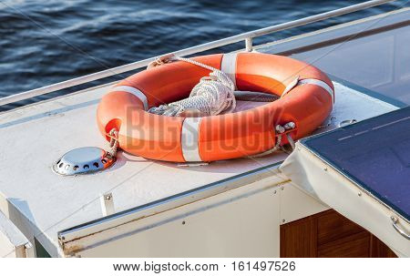 Vibrant orange lifebuoy on the excursion boat in summer day