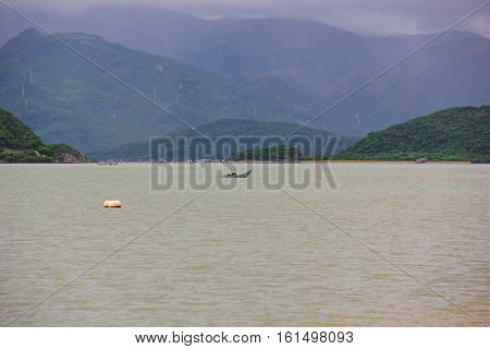 landscapes of Vietnam, greenish sea water, a small boat on the water, lots of mountains, hills, different height, covered with green plants, the clouds hanging over the mountain tops
