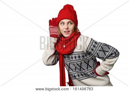 Young woman in winter warm clothing listening gossip with attention looking to the side at blank copy space