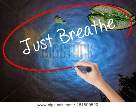 Woman Hand Writing Just Breathe With Marker Over Transparent Board