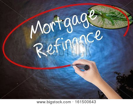 Woman Hand Writing Mortgage Refinance With Marker Over Transparent Board