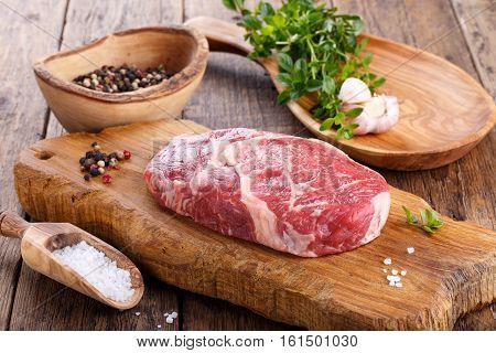 Raw beef rib eye steak on wooden