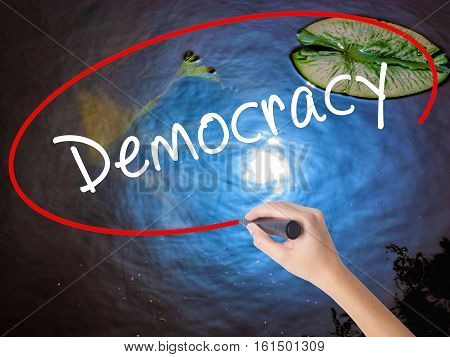 Woman Hand Writing Democracy With Marker Over Transparent Board