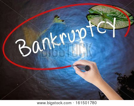 Woman Hand Writing Bankruptcy With Marker Over Transparent Board