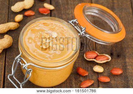 Peanut butter in a jar. Wooden spoon full of peanut butter.