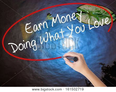 Woman Hand Writing Earn Money Doing What You Love With Marker Over Transparent Board