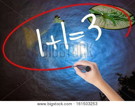 Woman Hand Writing 1+1=3 With Marker Over Transparent Board