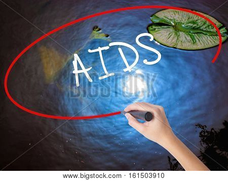 Woman Hand Writing Aids With Marker Over Transparent Board