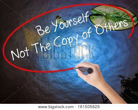 Woman Hand Writing Be Yourself Not The Copy Of Others With Marker Over Transparent Board