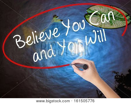 Woman Hand Writing Believe You Can And You Will With Marker Over Transparent Board