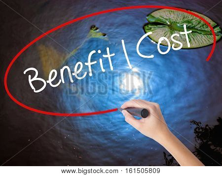 Woman Hand Writing Benefit Cost With Marker Over Transparent Board