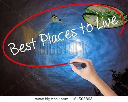 Woman Hand Writing Best Places To Live With Marker Over Transparent Board