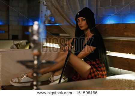 Beautiful Hipster Girl With Hat Smokes A Hookah. Sitting On The Couch In The Bar.