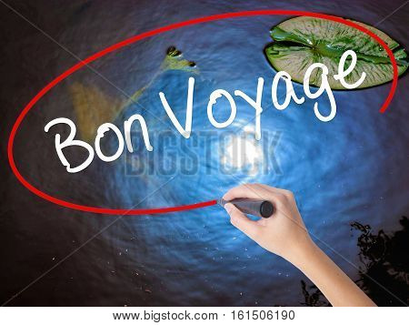 Woman Hand Writing  Bon Voyage  (have A Good Trip In French)  With Marker Over Transparent Board