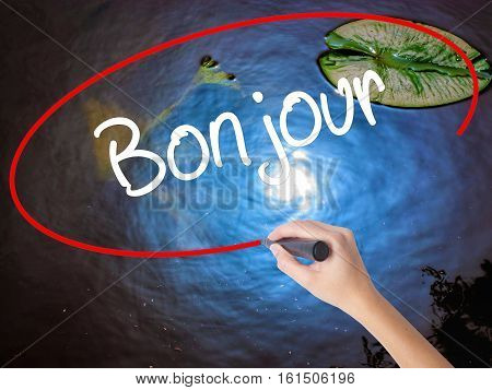Woman Hand Writing Bonjour  (good Morning In French) With Marker Over Transparent Board