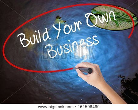 Woman Hand Writing Build Your Own Business With Marker Over Transparent Board.