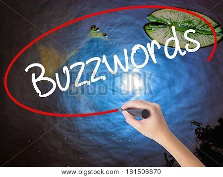 Woman Hand Writing Buzzwords With Marker Over Transparent Board