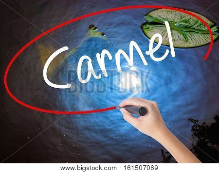 Woman Hand Writing Carmel With Marker Over Transparent Board