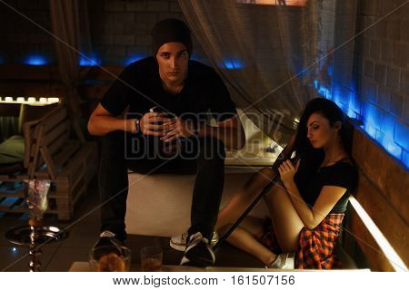 Fashion Boy And Girl Sitting On A Couch In A Nightclub.