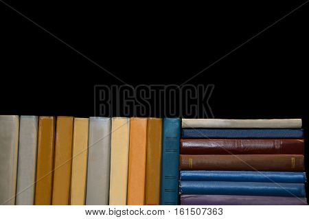 Old book on a black background. Is the library bookstore. Stack with book in multicolored covers. Reading paper book. Knowledge in textbook. Perorally sheets of ancient book.