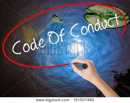 Woman Hand Writing Code Of Conduct With Marker Over Transparent Board