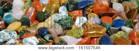 Semiprecious stones polished. Background of colorful minerals. Natural gems. The geological formation close. Smooth beautiful stones.
