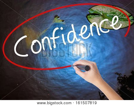 Woman Hand Writing Confidence With Marker Over Transparent Board