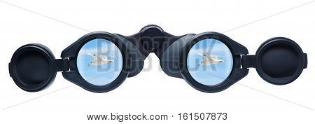 The sky with bird reflected in a pair of binoculars. Tourist binoculars isolated on a white background. Binoculars and blue sky concept of searching freedom