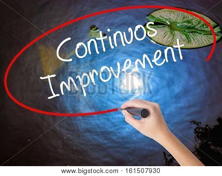 Woman Hand Writing Continuos Improvement With Marker Over Transparent Board