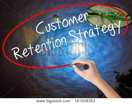 Woman Hand Writing Customer Retention Strategy With Marker Over Transparent Board