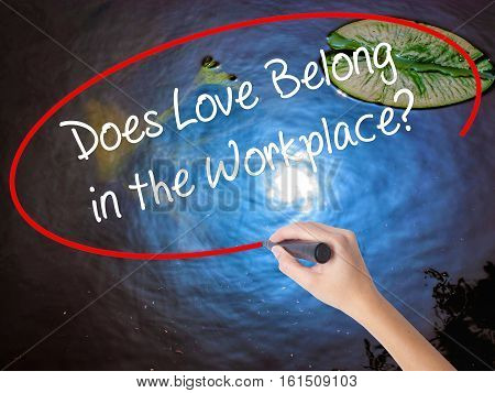 Woman Hand Writing Does Love Belong In The Workplace? With Marker Over Transparent Board