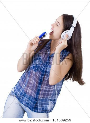 girl in headphones singing with her hairbrush as microphone isolated on white. Playful woman listening to music playing through her headphones and pretending to sing on a microphone that is actually a hairbrush.
