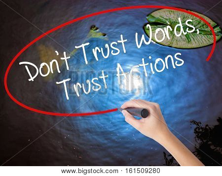 Woman Hand Writing Don't Trust Words, Trust Actions With Marker Over Transparent Board