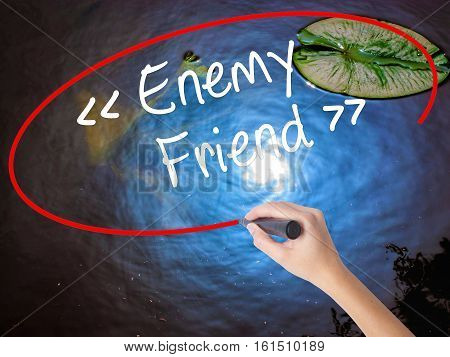 Woman Hand Writing Enemy - Friend With Marker Over Transparent Board.