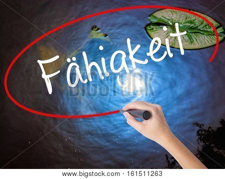 Woman Hand Writing Fahigkeit (ability In German) With Marker Over Transparent Board