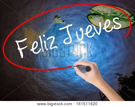 Woman Hand Writing Feliz Jueves (happy Thursday In Spanish) With Marker Over Transparent Board.