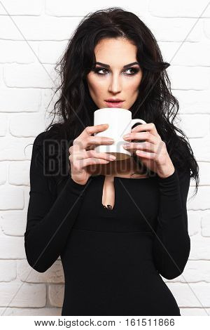 pretty cute sexy girl or beautiful young woman with fashion makeup on serious face and curly long brunette hair in black dress with deep neckline on slim body holds white cup on brick wall background