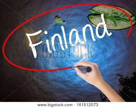 Woman Hand Writing Finland With Marker Over Transparent Board.