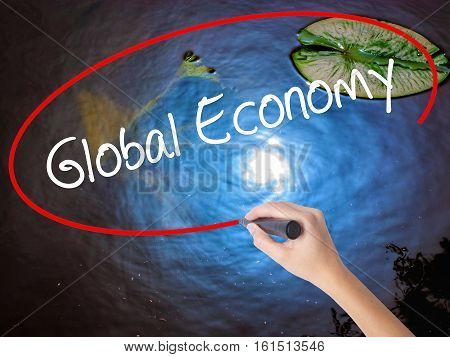 Woman Hand Writing Global Economy With Marker Over Transparent Board