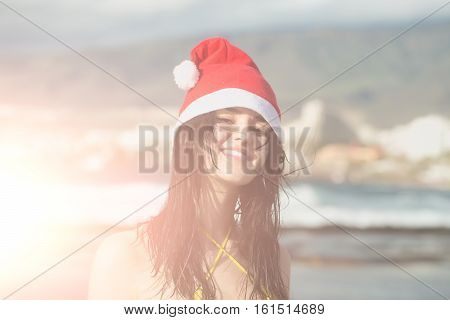 sexy santa claus cute girl or pretty young smiling woman with brunette hair in red new year hat and yellow swimsuit celebrates christmas or xmas holidays at beach sunny outdoor on natural background
