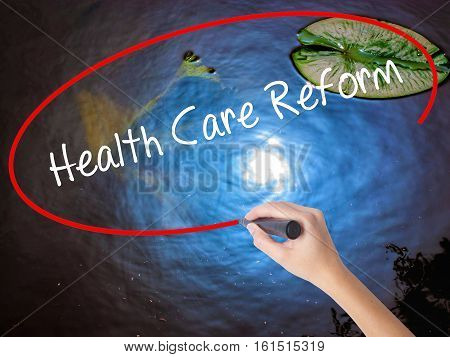 Woman Hand Writing Health Care Reform With Marker Over Transparent Board