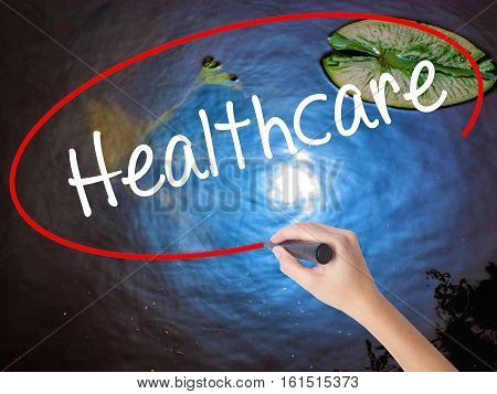 Woman Hand Writing Healthcare With Marker Over Transparent Board