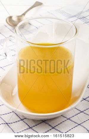 homemade chicken broth in a glass during the winter time well suited for cold