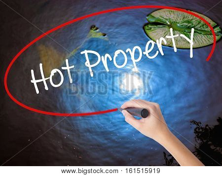 Woman Hand Writing Hot Property With Marker Over Transparent Board