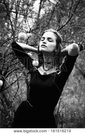 Young girl in a black dress posing in autumn bare thin twigs with little white apples on them black and white