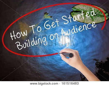 Woman Hand Writing How To Get Started Building On Audience With Marker Over Transparent Board
